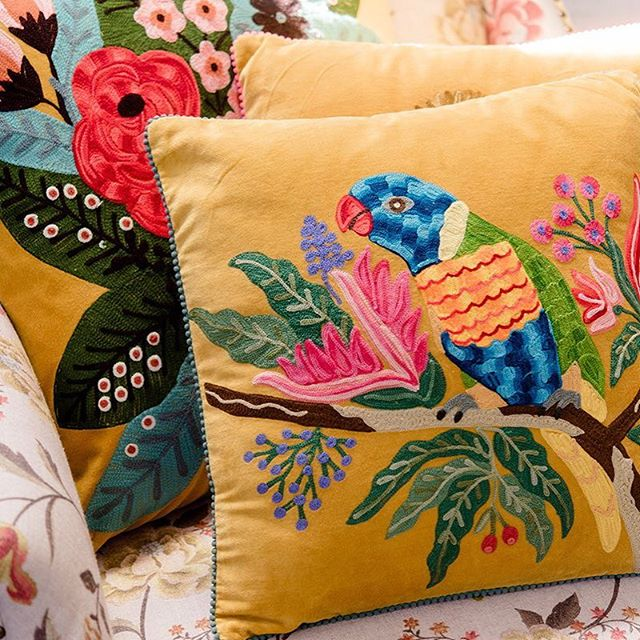 Embroidered lorikeet on mustard velvet cushion