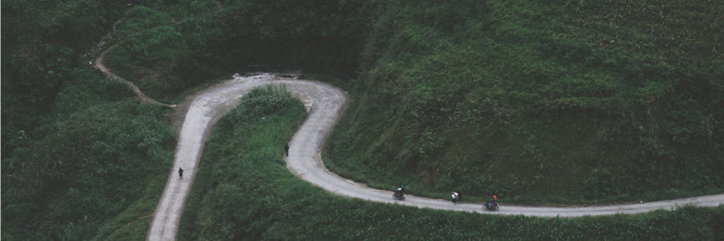 People riding a bike on a road in a mountain in Vietnam