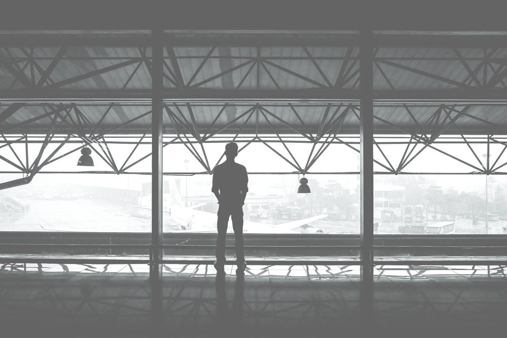 Black and white photo of a man standing in front of a airport window looking at a parked airplane