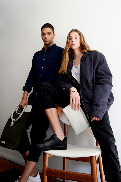 Guy and Girl looking at camera - Holding two bags from Von-Routte