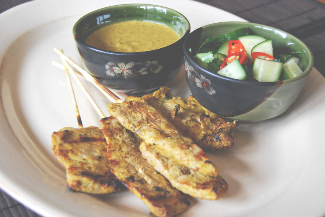 Plate with pork skewers, satay sauce and cucumber salad