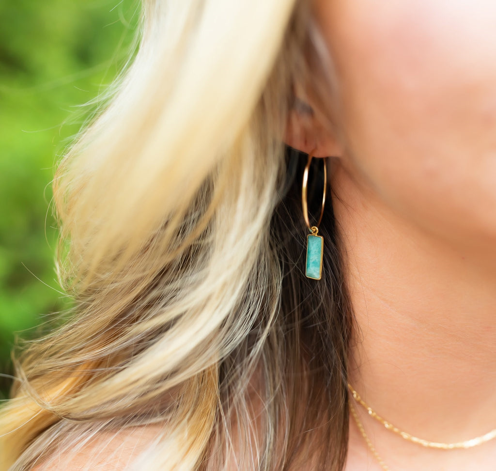 green amazonite hoop earrings on a blond wavy haired woman.