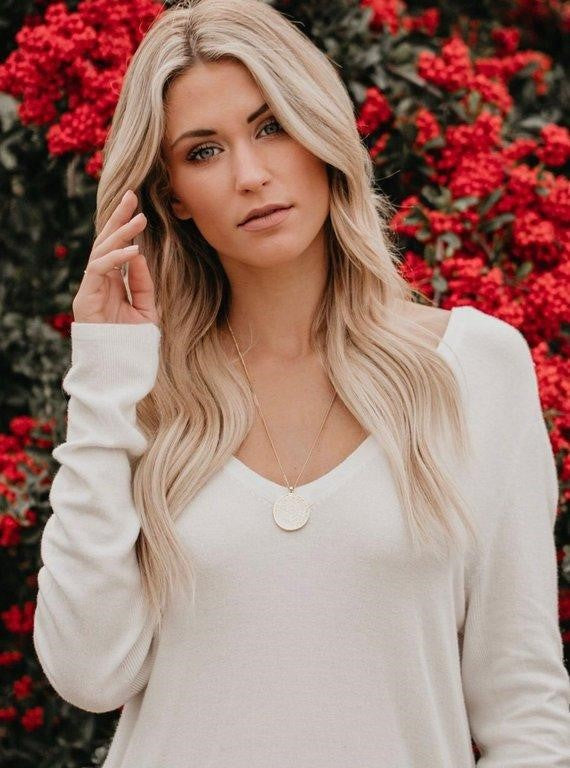 Athens gold medallion necklace by Meghan Bo Designs on Vici Collection model with long blond hair wearing a white shirt holding her right hand up to her face.