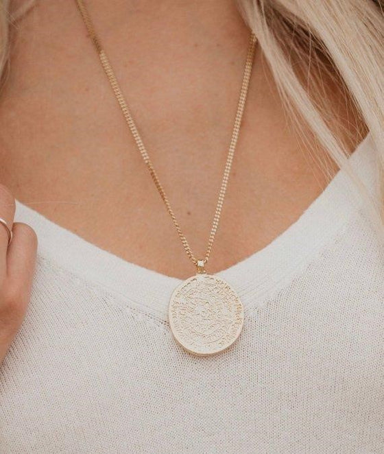 Gold coin medallion necklace by meghan bo designs on vici collection model wearing a white shirt.
