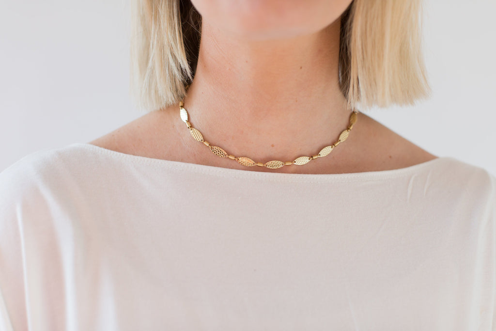 A short haired blonde woman wearing a vici collection white shirt and a gold bohemian glam choker necklace by Meghan Bo designs.