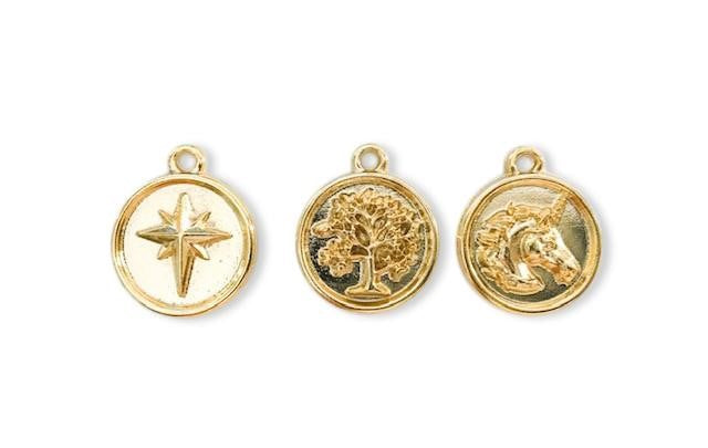 Three gold coin charms, a star, a tree and a unicorn head lay on a white surface.