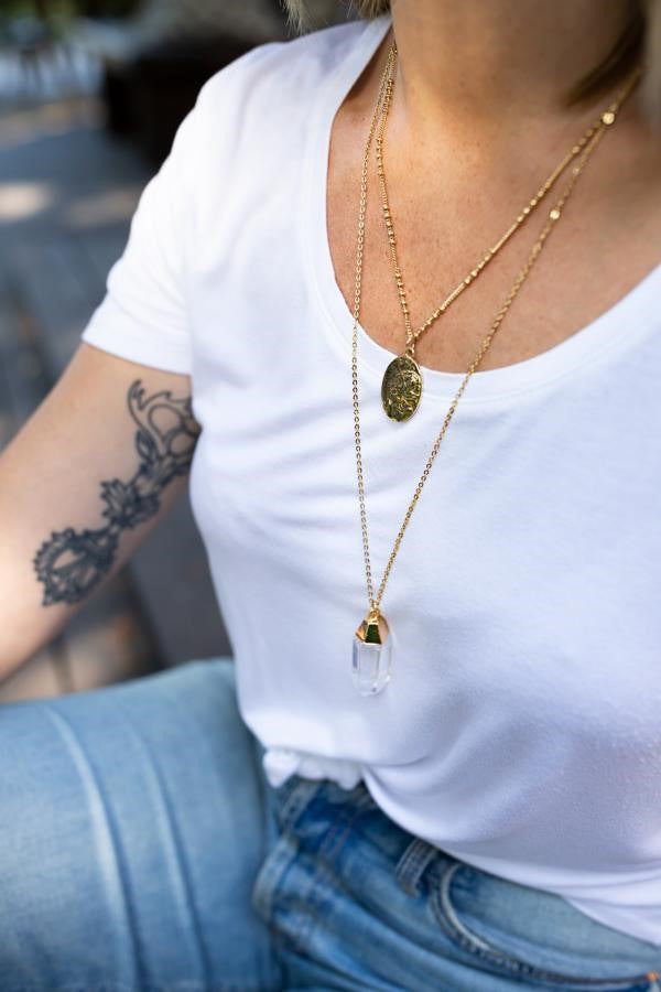 A woman with short brown hair wearing a white scoop neck tee shirt and jeans has tattoo on her inner right bicep is wearing layered necklaces by Meghan Bo Designs including the Dandelion Necklace and Crystal Quartz Pendant necklace.