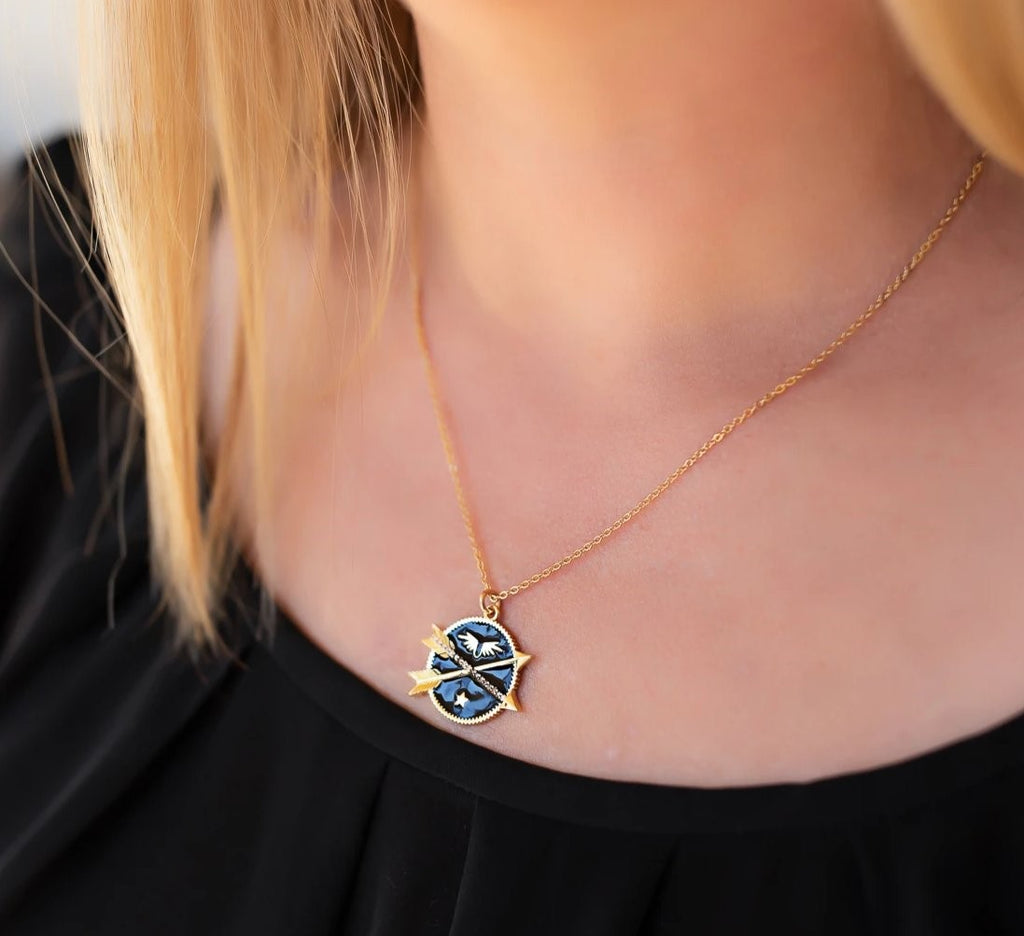 A woman with shoulder length blonde hair wearing a black scoop neck tee shirt is wearing a black enamel coin necklace with two crossing arrows, a star and wings on a heavy gold overlay chain by Meghan Bo Designs, the Double Arrow Adventure Necklace.