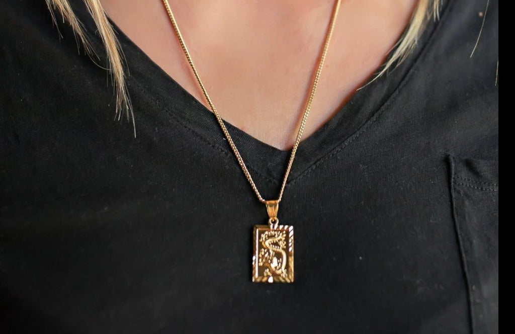 A woman with blonde hair wearing a black v neck tee shirt is wearing a gold Dragon necklace that is a rectangle shape by Meghan Bo Designs.