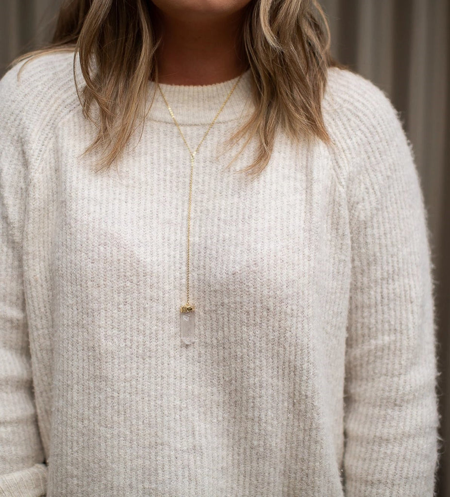 A woman with medium length blonde hair wearing a white sweater is wearing Meghan Bo Designs Eve Crystal Lariat Necklace in gold with a quartz crystal pendant hanging down the middle.