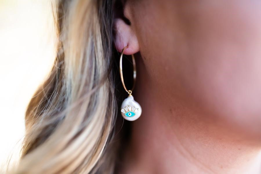A woman with blonde hair is wearing gold fill hoop earrings with a pearl pendant that has a blue evil eye on it made by Meghan Bo Designs.