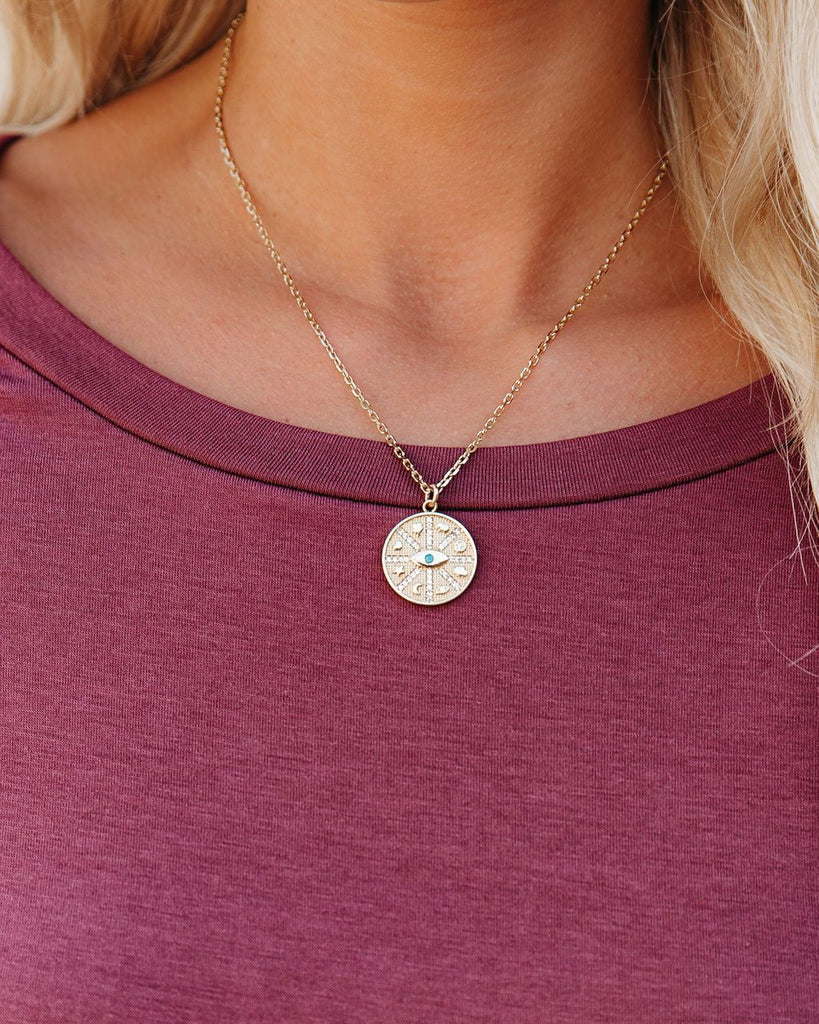 A blonde woman wearing a pink vici collection scoop neck shirt is wearing the fortune coin medallion necklace in gold made by Meghan Bo Designs with a hamsa hand, elephant, evil eye, moon, star and peace sign.