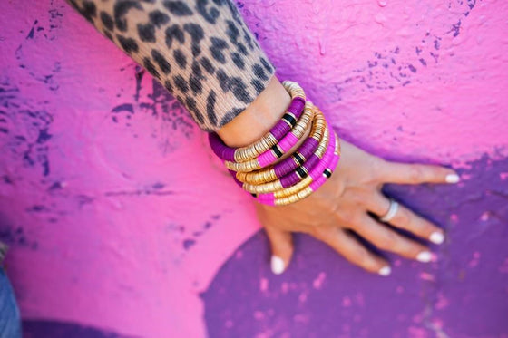 A woman's hand lays on a pink and purple wall, with stacked purple and pink gold bracelets on wrist wearing a leopard print sweater made by Meghan Bo Designs.
