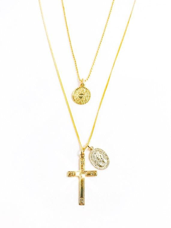 Two layered necklaces, one has a small coin pendant with the Our Father prayer inscribed and a necklace with a gold fill cross and sterling silver saint pendant made by Meghan Bo Designs.