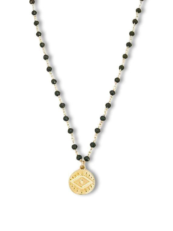 A black rosary chain with a small gold coin pendant that has an evil eye on it necklace made by Meghan Bo Designs lays flat on a white surface.