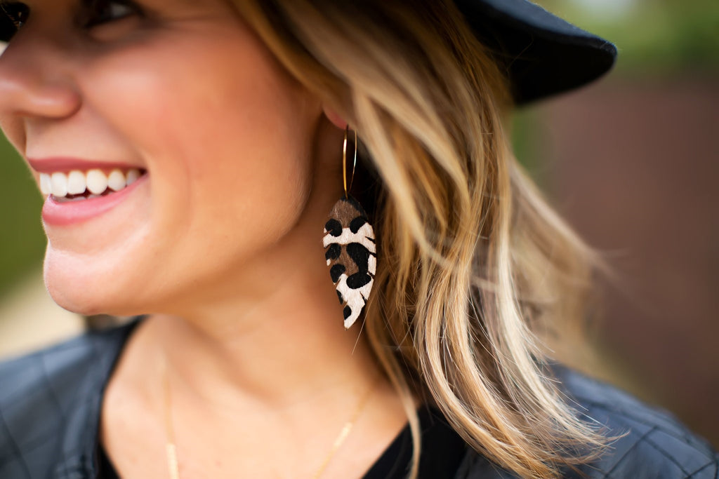 A woman wit blonde hair is wearing a black hat and black leather jacket, she is looking off to the side and wearing leopard faux fur earrings made by Meghan Bo Designs.
