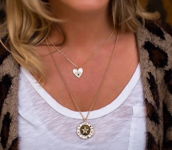 A woman wearing a leopard print cardigan from vici collection and a white scoop neck tee shirt is wearing two layered necklaces, one with a white enamel heart and evil eye and the other is a white enamel coin necklace with a star in the middle made by Meghan Bo Designs.