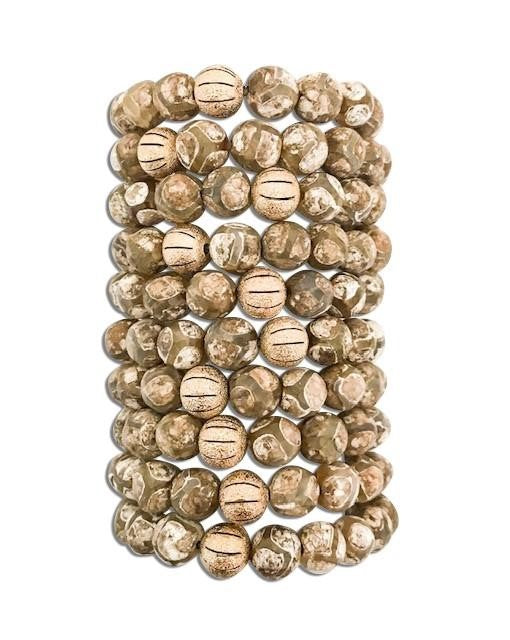 A natural stone essential oil  bracelet stack with gold accent beads made by Meghan Bo Designs lays on a white surface.