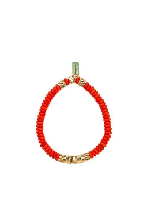 An orange heishi beaded bracelets with gold accent beads made by Meghan Bo Designs lays on a white surface.