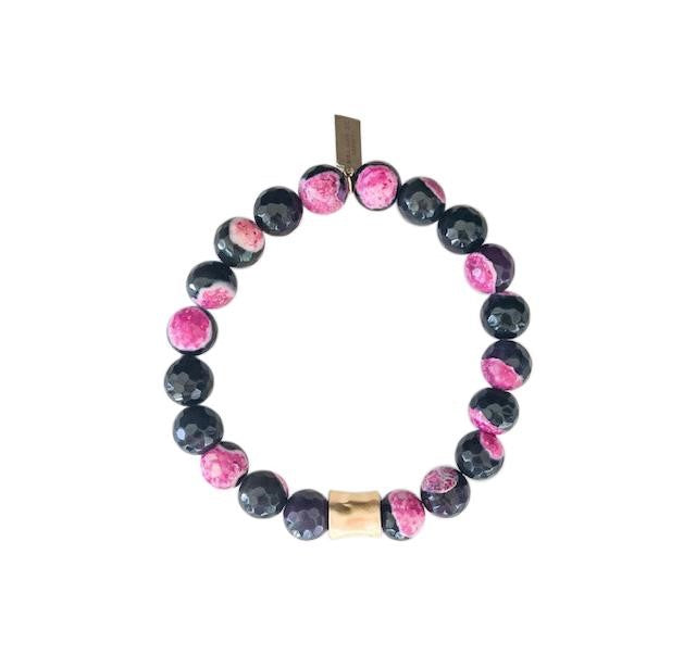 A pink and black fire agate beaded bracelet with a gold accent bead lays on a white surface made by Meghan Bo Designs.