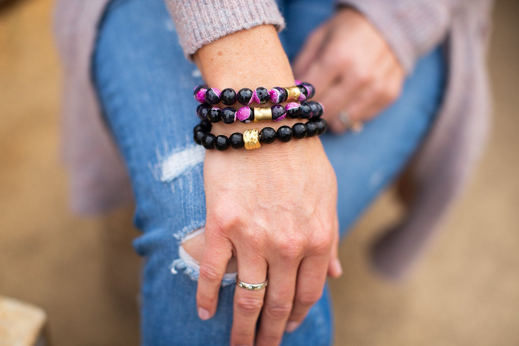 A woman wearing jeans and a cardigan is crossing her legs with her hands over her knee, she is wearing a stack of beaded stretch bracelets that have pink and black fire agate beads with gold accents made by Meghan Bo Designs.