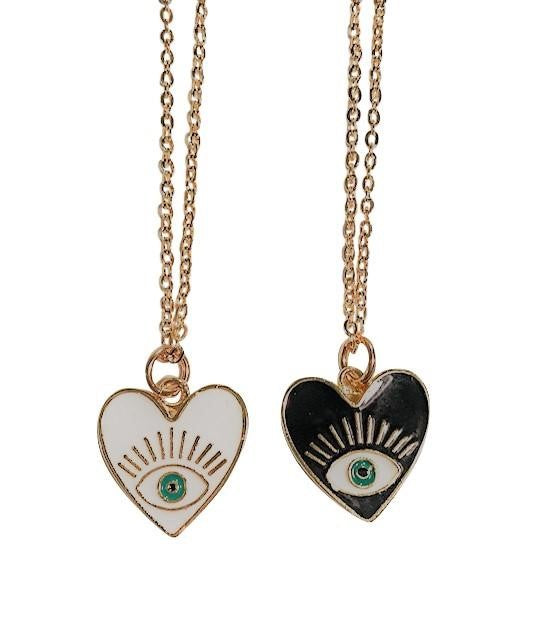 Two necklaces on gold chains lay on a flat white surface, the pendants are heart shaped with an evil eye in the middle, one is white and one is black made by Meghan Bo Designs.