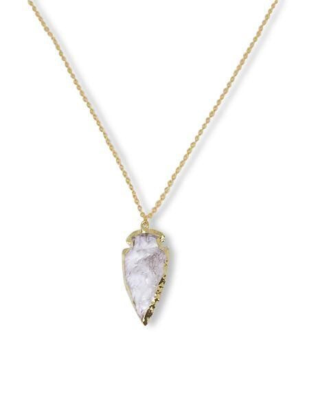 A gold chain with a clear quartz arrowhead edged in gold made by Meghan Bo Designs.