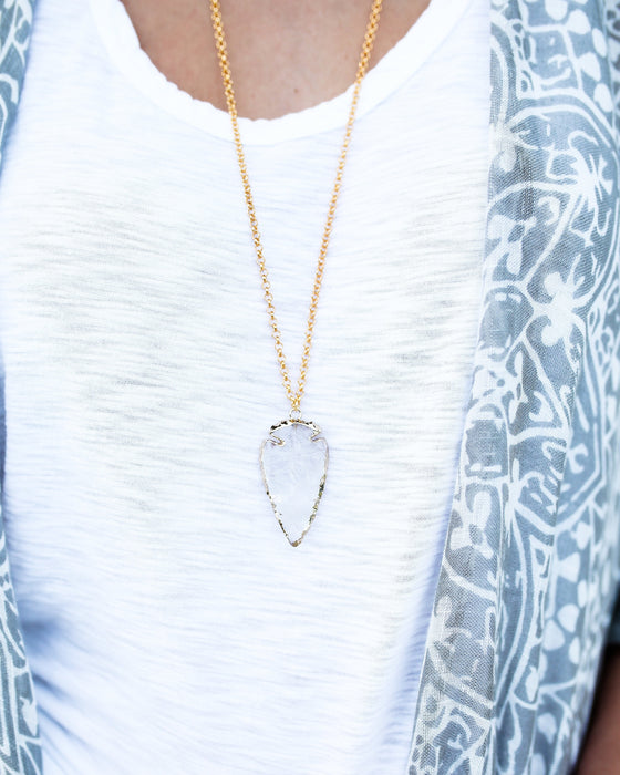 A woman is wearing a white scoop neck tee shirt from vici dolls with a long gold necklace that has a clear quartz arrowhead pendant edged in gold made by Meghan Bo Designs.