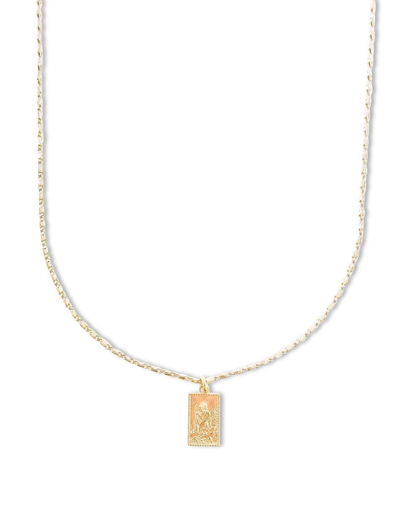 A gold rectangle Saint Christopher pendant on a gold chain made by Meghan Bo Designs lays on a flat white surface.