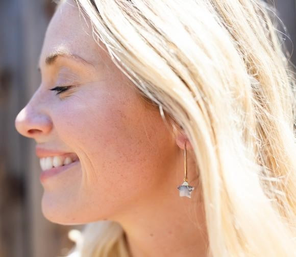A profile of a blonde woman is closing her eyes and smiling, she is wearing gold fill hoop earrings with a small gemstone star hanging from them made by Meghan Bo Designs.