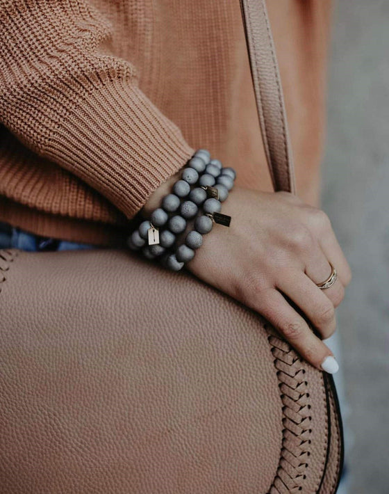 A woman wearing a brown vici sweater and tan vici purse is wearing a stack of silver beaded stretch bracelets made by Meghan Bo Designs.