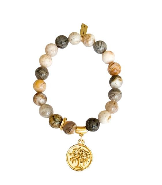 A beaded bracelet made with neutral colored beads has gold accent beads and a tree gold coin charm made by Meghan Bo Designs lays on a flat white surface.