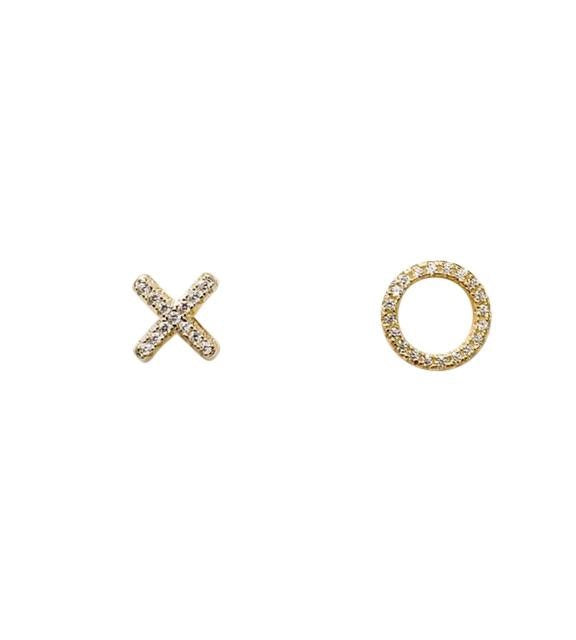 "A pair of cubic zirconia initial earrings, an ""X"" and an ""O""  made by Meghan Bo Designs lay on a flat white surface."