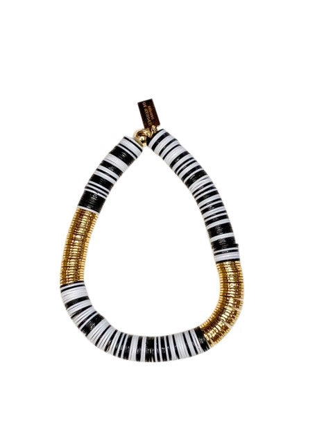 A heishi beaded bracelet with black and white vinyl beads with gold accents made by Meghan BO Designs lays on a white surface.