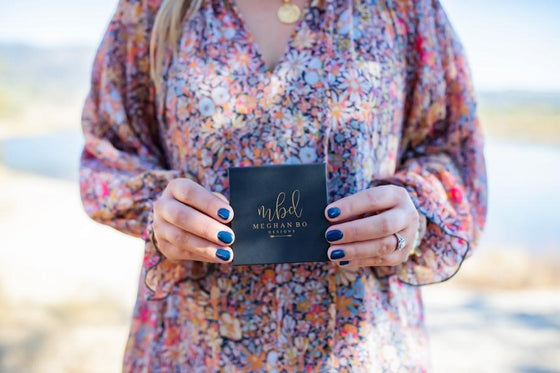A woman wearing a long floral Free People dress holding a black Meghan Bo Designs jewelry box with blue dip nails.