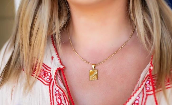 A blonde haired woman wearing a bohemian red dress and Meghan Bo Designs Brilliance Tag gold necklace which is handmade in Sonoma, California.