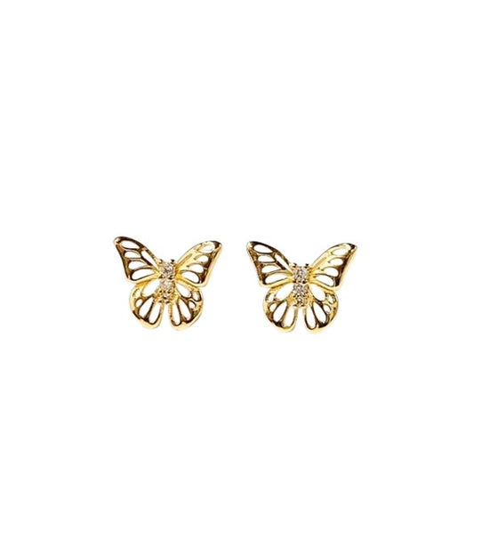 A gold pair of butterfly stud earrings with 3 small cubic zirconia made by Meghan Bo Designs lay on a flat white surface.