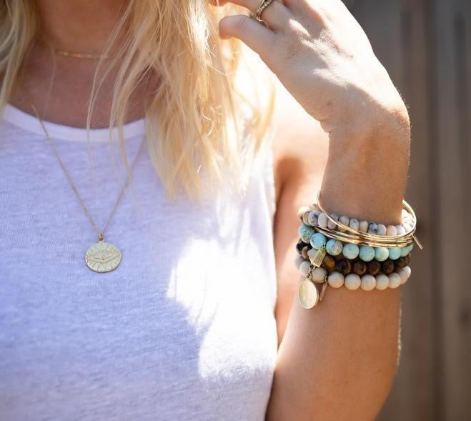 A blond woman wearing a white tank top, layered Meghan Bo Designs necklaces, the Legend Evil Eye Coin Medallion and the Katie Choker along with a stack  of Meghan Bo Designs beaded stretch bracelets on her left arm, gold fill bangles, calming agate, tiger eye and riverstone gemstones.