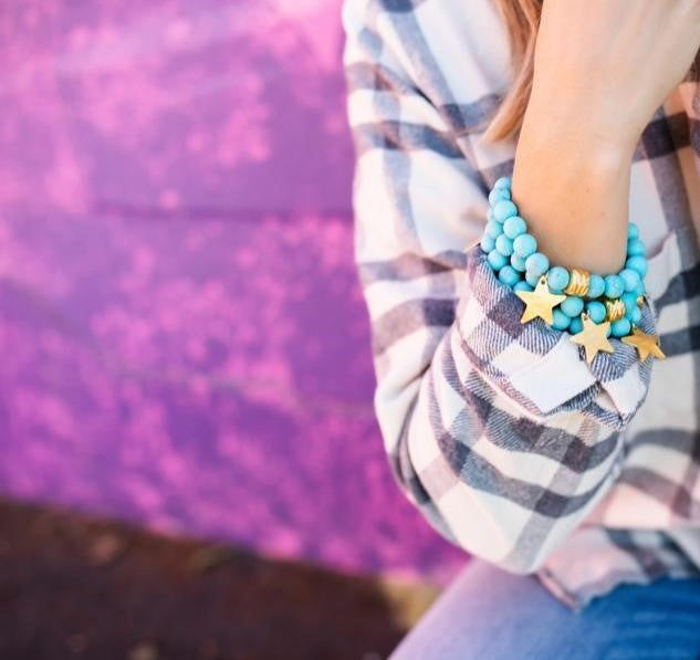 A woman sitting in front of a pink graffiti wall wearing a flannel shirt, jeans and Meghan Bo Designs celestial star matte turquoise beaded stretch bracelet stack.