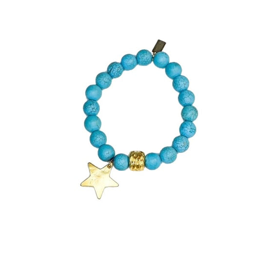A turquoise beaded bracelet with a gold accent bead and a gold star charm made by Meghan Bo Designs lays on a flat white surface.