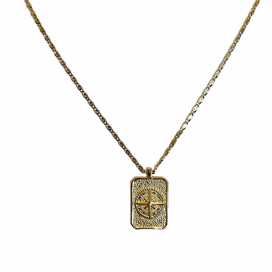 A gold rectangle pendant with a compass and a star hang on a detailed gold chain made by Meghan Bo Designs.