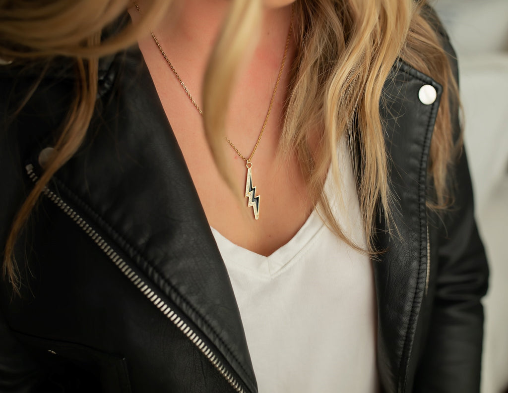 A woman with long blonde hair wearing a black leather jacket, white v neck tee shirt and an edgy cubic zirconia lightning bolt necklace on a gold chain by Meghan Bo Designs.