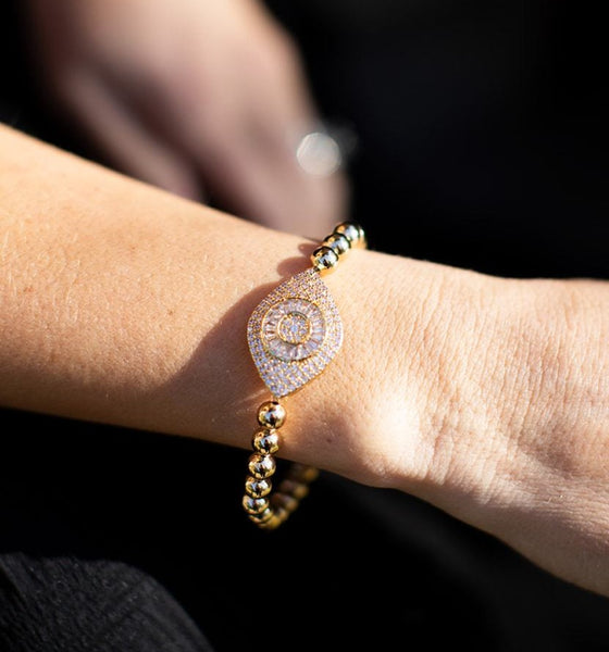 A woman wearing a black VICI Collection dress sits with her right arm out wearing a gold beaded bracelet with a large cubic zirconia evil eye in the middle of it made by Meghan Bo Designs.