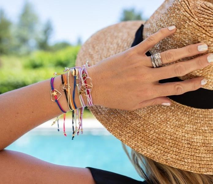 A woman wearing a sun hat with her left hand touching the top of the hat is staring at a pool and wearing a stack of colorful adjustable friendship bracelets made by Meghan Bo Designs.