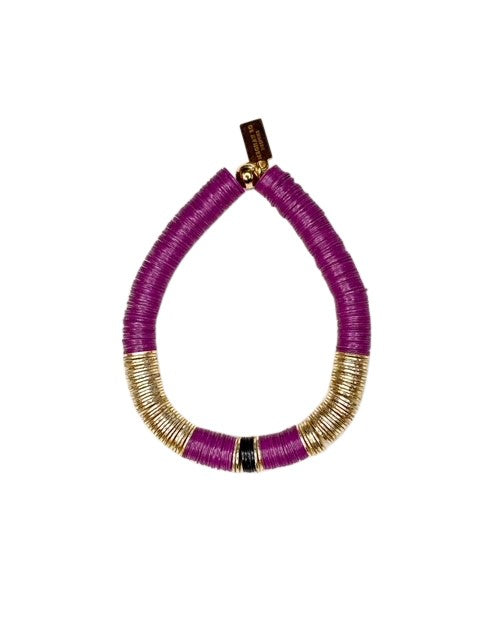A purple heishi beaded bracelet with gold accents made by Meghan Bo Designs lays on a flat white surface.