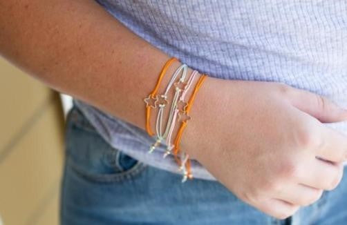 A woman wearing a gray shirt and jeans is hold up her right arm while wearing a stack of adjustable friendship bracelets in multiple colors with a gold star made by Meghan Bo Designs.