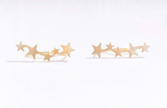 An ear climber with five gold stars ranging in size for an earring that requires no piercing made by Meghan Bo Designs.