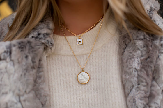 A woman with blonde hair is wearing a faux fur gray jacket, a white sweater and layered necklaces; one has a square white star and the other is a pearl pendant with a saint on it made by Meghan Bo Designs.