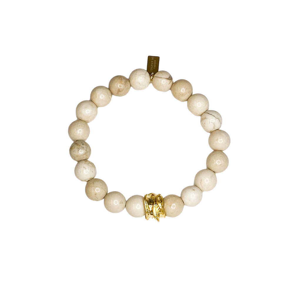 A white beaded bracelet with a gold accent bead made by Meghan Bo Designs lay on a flate white surface.