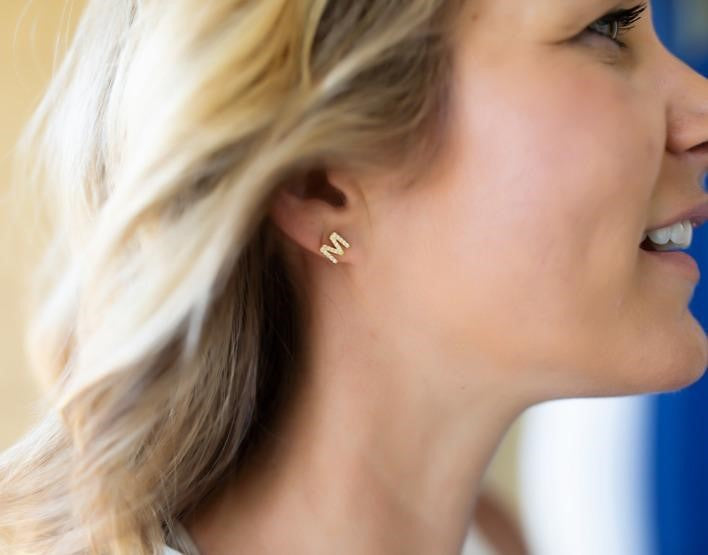"A woman with blonde hair is smiling and looking off to the side, she is wearing an ""M"" initial earring made by Meghan Bo Designs."
